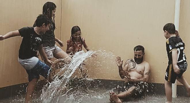 Duca Tambasco do Oficina G3, na chuva com crianças