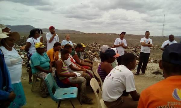 Pessoas no lixão ouvindo a Associação Vitoria nas missões