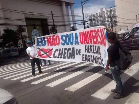 Dois homens segurando faixas contra a igreja universal